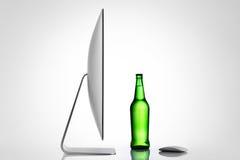 Botella aislada del ordenador y de cerveza en un fondo blanco Foto de archivo