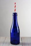Botella azul con la paja rayada roja Imagenes de archivo