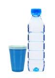 Botella azul con las tazas del agua y del plástico aisladas en blanco Imagen de archivo