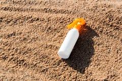 Botella blanca de la loci?n del bronceado en la arena con el espacio de la copia crema del spf del sunblock en la playa del mar e foto de archivo