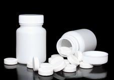 Botella blanca de la medicina, píldoras del color en negro. Fotos de archivo