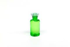 Botella clara plástica de empaquetado con el líquido verde en el fondo blanco aislado Imágenes de archivo libres de regalías