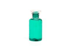 Botella clara plástica de empaquetado con el líquido verde en el fondo blanco aislado Fotografía de archivo libre de regalías