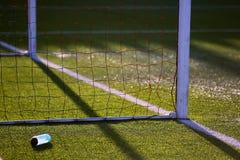 Botella con agua cerca de las puertas del fútbol en campo artificial del césped Foto de archivo libre de regalías