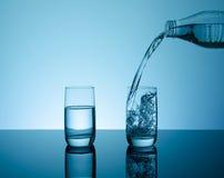 Botella con agua que salpica creativa en el vidrio Imágenes de archivo libres de regalías