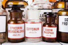 Botella con cafeína entre otras botellas de la medicina del vintage imagen de archivo libre de regalías