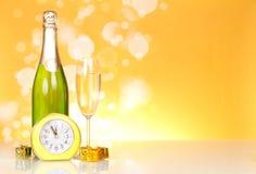 Botella con champán, pequeñas sorpresas del Año Nuevo y el reloj Fotografía de archivo