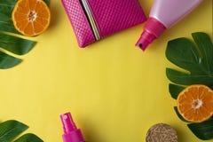 Botella con crema del bronceado en el fondo amarillo, adornado con las hojas del monstera Fondo abstracto del verano Plantilla pa imagenes de archivo
