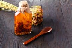 Botella con el aceite vegetal con las hierbas en una tabla rústica de madera Imagen de archivo libre de regalías