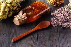 Botella con el aceite vegetal con las hierbas en una tabla rústica de madera Imagen de archivo