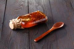 Botella con el aceite vegetal con las hierbas en una tabla rústica de madera Fotos de archivo