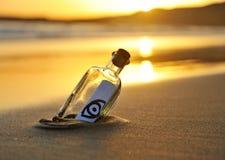 Botella con el icono en la playa, tarde del ojo fotografía de archivo