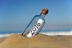 botella 2016 con el mensaje del Año Nuevo en la playa Imagen de archivo libre de regalías