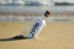 botella 2016 con el mensaje del Año Nuevo en la playa Foto de archivo libre de regalías