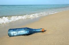 Botella con el mensaje en orilla imagenes de archivo