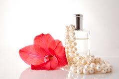 Botella con el perfume, un collar de la perla una flor Foto de archivo libre de regalías