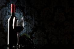 Botella con el vino rojo y el vidrio en una piedra vieja Imágenes de archivo libres de regalías