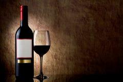 Botella con el vino rojo y el vidrio en una piedra vieja Fotografía de archivo