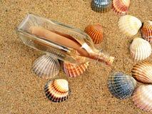 botella con la carta en una playa Foto de archivo