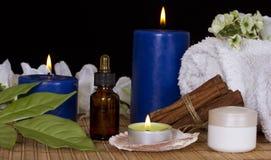 Botella con la esencia del balneario, las velas del balneario, las flores y la crema Foto de archivo