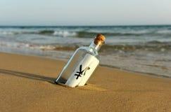 Botella con la muestra de yenes en la arena de la playa, concepto del dinero imagenes de archivo