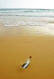 Botella con la muestra euro en la arena de la playa Fotografía de archivo libre de regalías