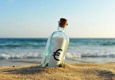 Botella con la muestra euro en la arena de la playa Imagen de archivo