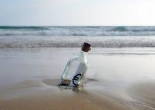 Botella con la muestra euro en la arena de la playa Imagen de archivo libre de regalías