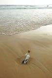 Botella con la muestra euro en la arena de la playa Imágenes de archivo libres de regalías