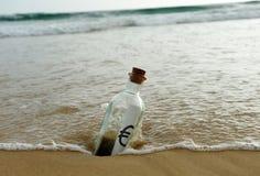 Botella con la muestra euro en la arena de la playa Fotos de archivo libres de regalías