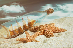 Botella con la nave dentro en la playa Foto de archivo