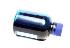 Botella con la pintura azul aislada en el fondo blanco Fotografía de archivo