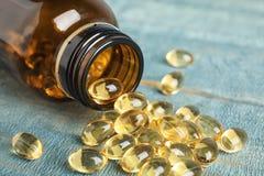 Botella con las píldoras del aceite de hígado de bacalao en la tabla imágenes de archivo libres de regalías