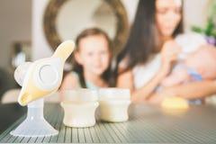 Botella con leche y la bomba de lactancia manual Imagenes de archivo