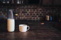 Botella con leche y una taza en una tabla de madera imágenes de archivo libres de regalías