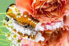 Botella con los glóbulos de la homeopatía que ponen en un espejo fotos de archivo