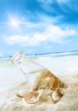 Botella con los seashells en la arena Foto de archivo libre de regalías