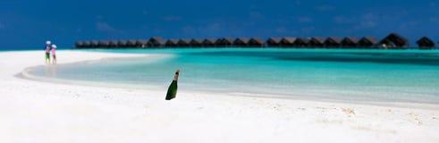 Botella con un mensaje en la playa tropical Foto de archivo