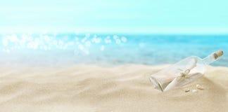 Botella con un mensaje en la playa fotografía de archivo