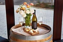 Botella, copas de vino con el vino blanco y aperitivo del queso en barra Foto de archivo