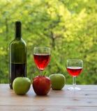 Botella, copas de vino rojas y manzanas verdes en la tabla Foto de archivo