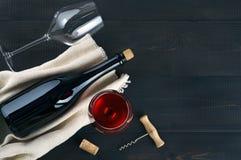 Botella, copas de vino y sacacorchos en la tabla oscura fotografía de archivo libre de regalías