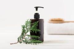 Botella cosmética de Brown, rama del abeto Fondo blanco balneario y cuerpo c Fotografía de archivo