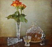 Botella cristalina del brandy con las rosas Foto de archivo