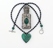 Botella cristalina verde del collar y de perfume aislada Fotos de archivo