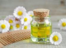 Botella de aceite cosmético de la manzanilla y de peine de madera del pelo Fotografía de archivo libre de regalías