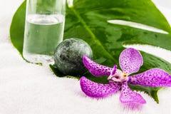 Botella de aceite de coco, piedra del huevo con las orquídeas rosadas del mokara y verde Fotografía de archivo