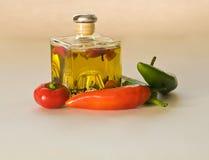 Botella de aceite de cristal con pimientas Foto de archivo