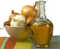 Botella de aceite de oliva con la cebolla y el ajo Foto de archivo libre de regalías