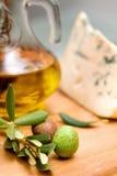 Botella de aceite de oliva en el vector y el queso de madera viejos Imágenes de archivo libres de regalías